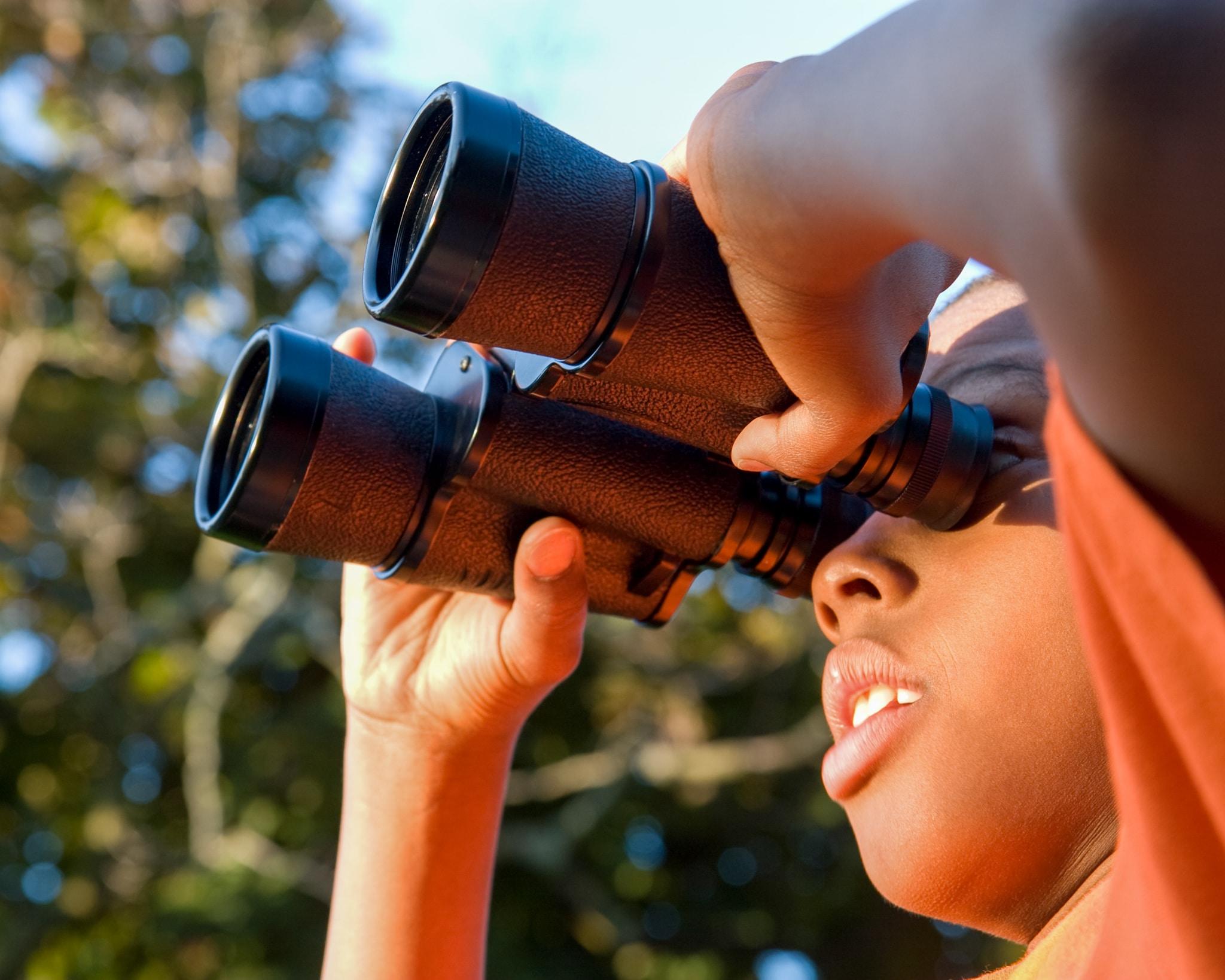 a boy looking through binoculars